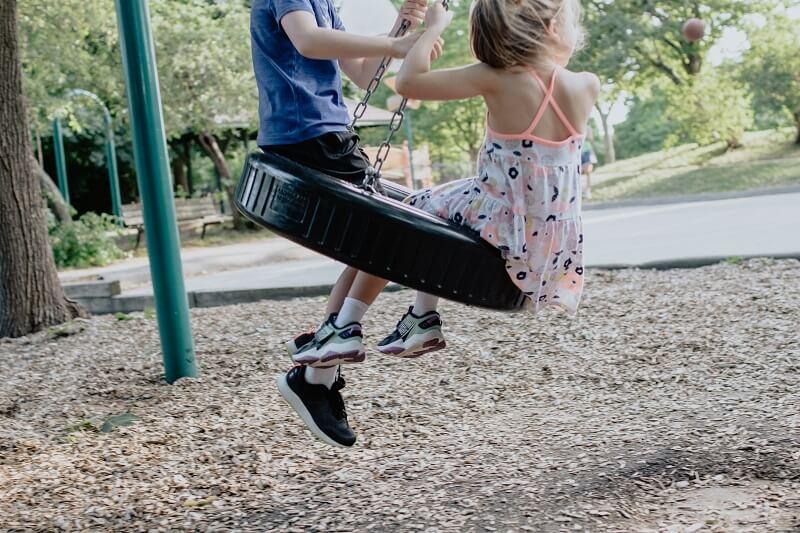 deux enfants sur une balançoire