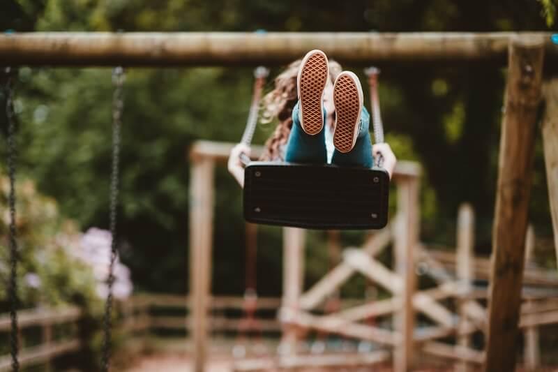 enfant faisaint de la balançoire dans une aire de jeux