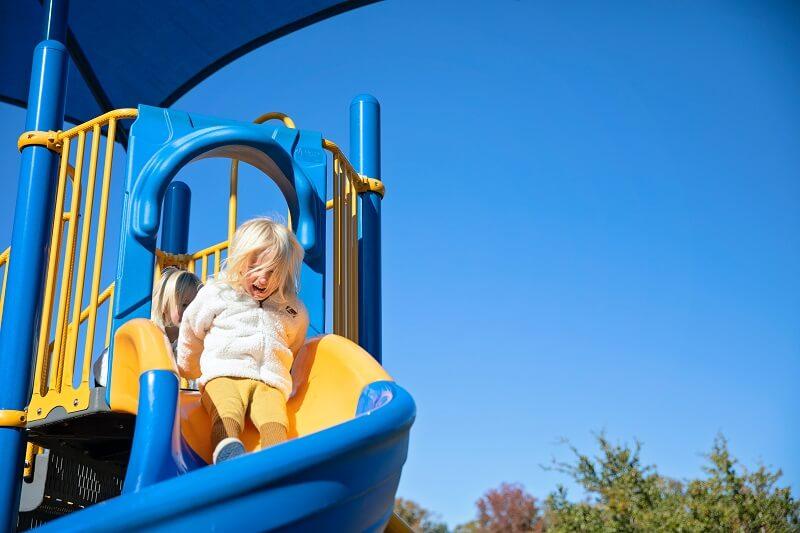 Aire de jeux exterieur enfant guide d'achat ultime avec une petite fille qui fait de la balancoire