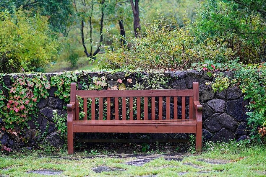 un banc de jardin devant un petit muret