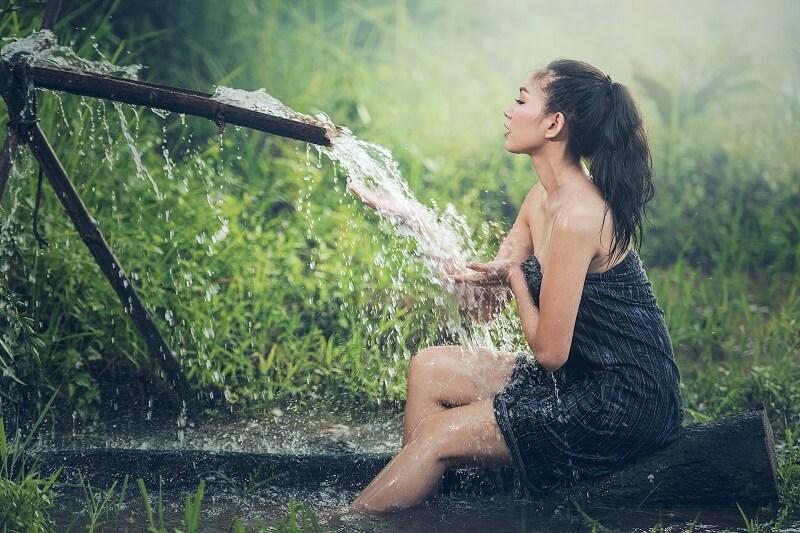 une femme se lavant avec un jet d'eau
